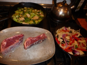 Pak choi, sauteed peppers and onions, and NY steaks before broiling
